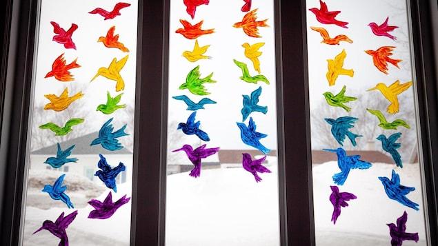 une fenetre avec des oiseaux peints aux couleurs de l'arc-enciel