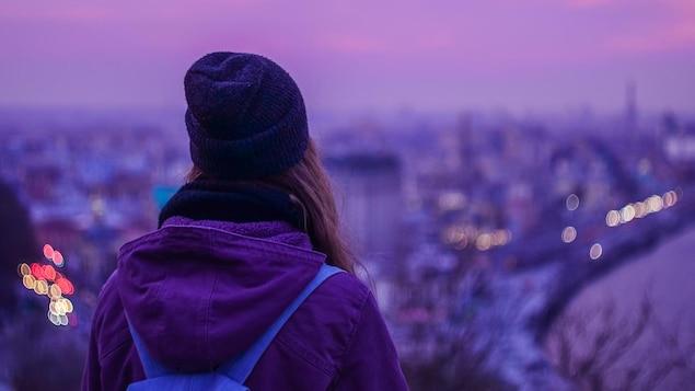 Une jeune femme portant une tuque est photographiée de dos regardant une ville au loin.