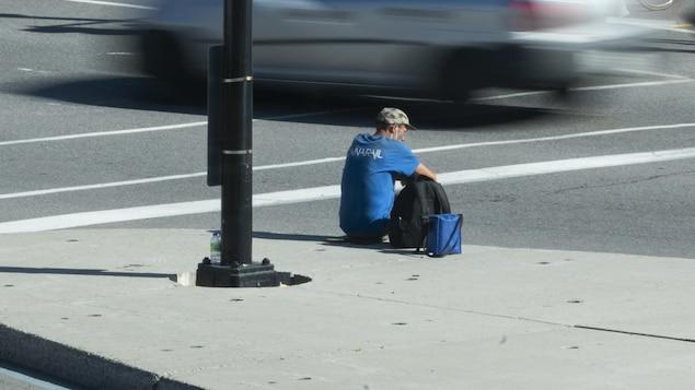 Un homme assis sur un terre-plein au milieu de la circulation.