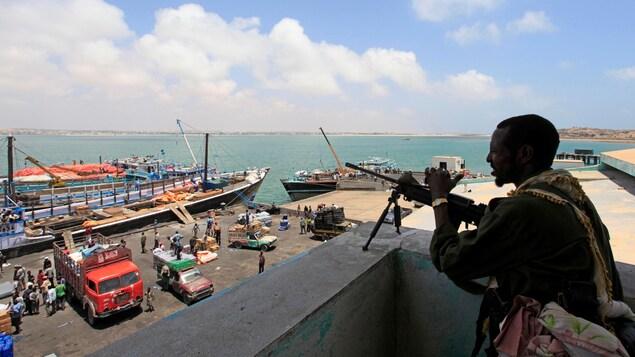 Un homme armé d'une mitraillette regarde le port de son poste de surveillance.