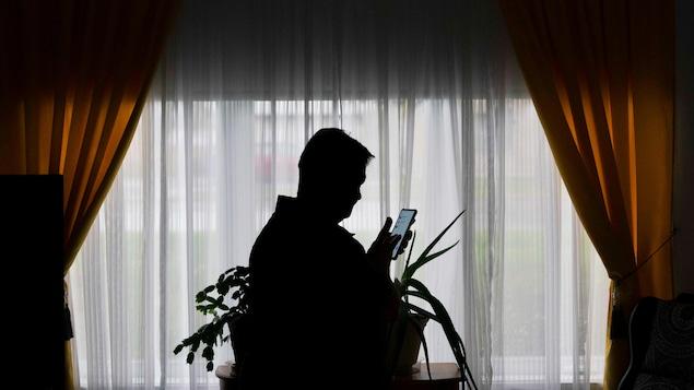 Une femme consulte son cellulaire.