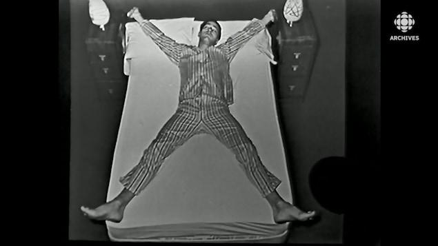 Un homme en pyjama long fait l'étoile en dormant dans un lit.