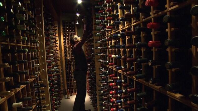 Un homme saisit une bouteille de vin parmi plusieurs autres entreposées dans une cave à vin à l'éclairage tamisé.