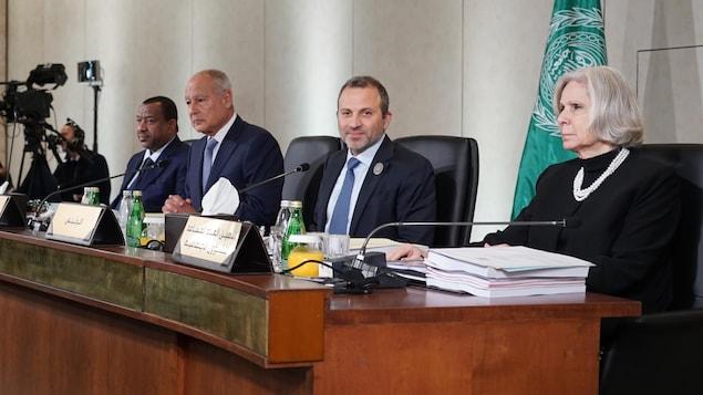 Trois hommes et une femme qui participent au sommet.