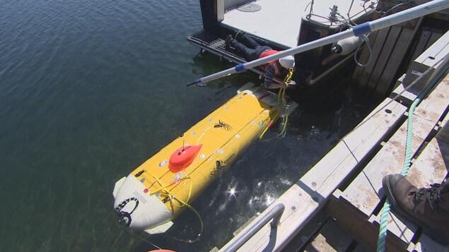 Des techniciens mettent à l'eau un petit véhicule sous-marins