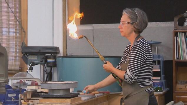 Sonia Beauchesne manipule une torche dans son atelier.