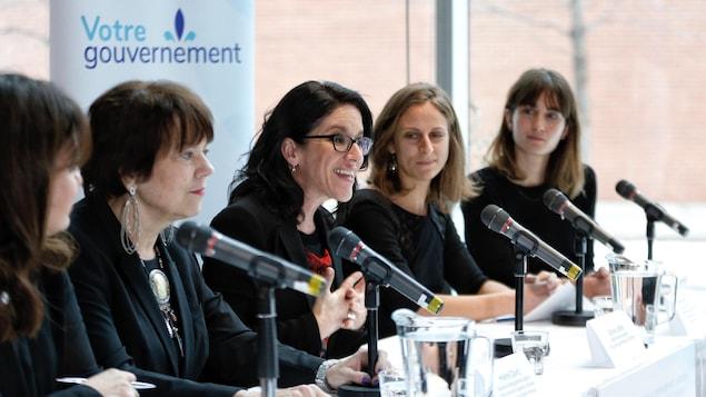Les cinq femmes derrière une table et des micros.