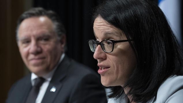 Sonia LeBel parle en point de presse, François Legault se trouve en arrière-plan.