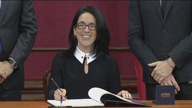 Sonia Lebel qui s'apprête à signer.