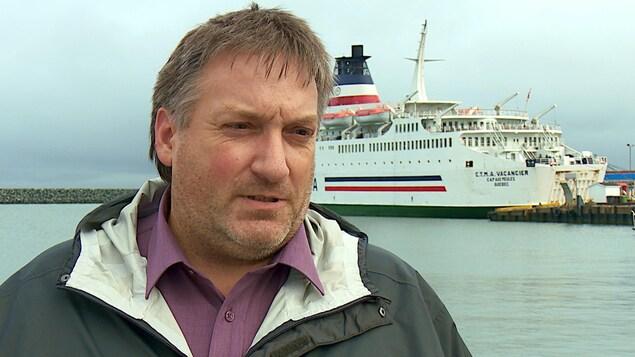 Le directeur défend les intérêts de la CTMA devant un des bateaux de la coopérative.