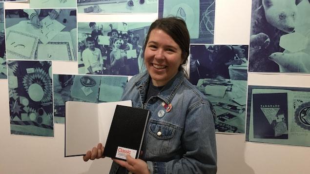 Une jeune souriante portant un veston de jeans est debout devant une murale et a deux cahiers de dessins dans les mains