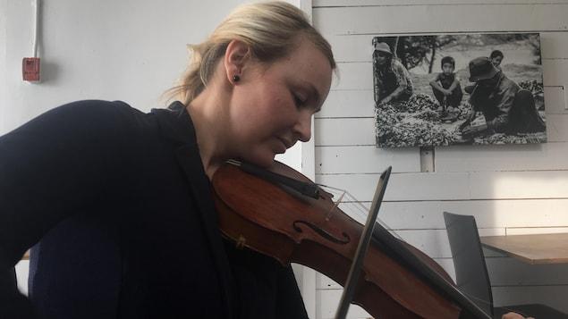 Sophie Lavoie pose son archet sur les cordes d'un violon.