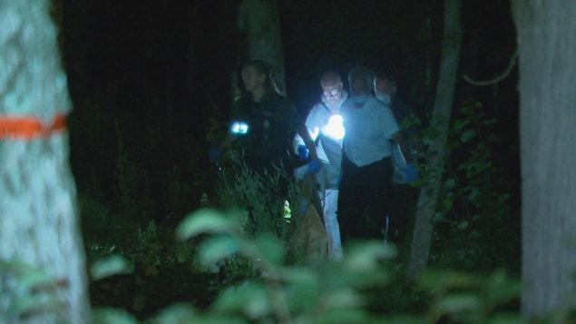 Des policiers portent un corps dans un boisé.