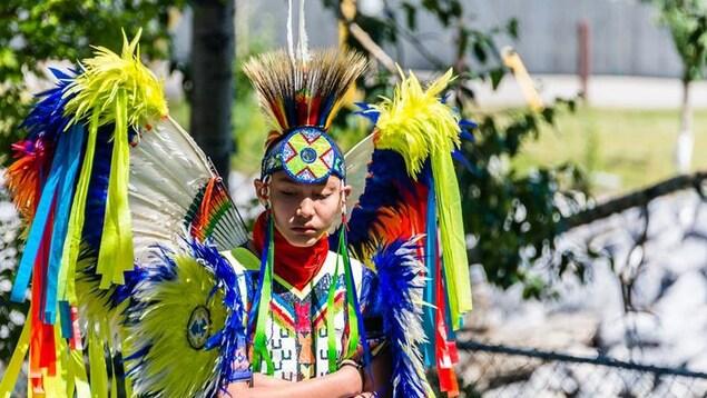 Un jeune autochtone porte les habits traditionnels de la célébration du Powwow