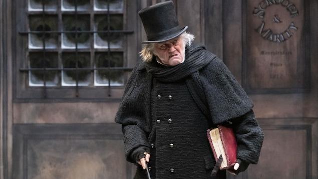 Le personnage Scrooge, un homme grincheux habillé en noir avec son chapeau et sa canne.