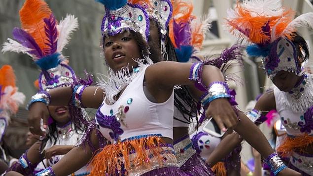 Une femme portes des costumes en plumes et des brillants pour le festival des caraïbes