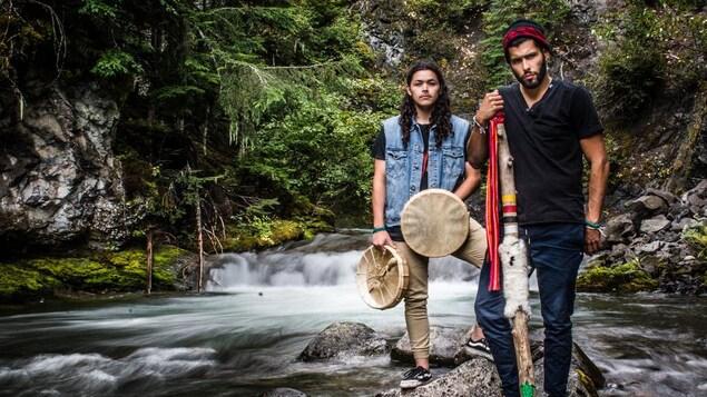 Deux hommes se tiennent debout sur une pierre, devant une chute