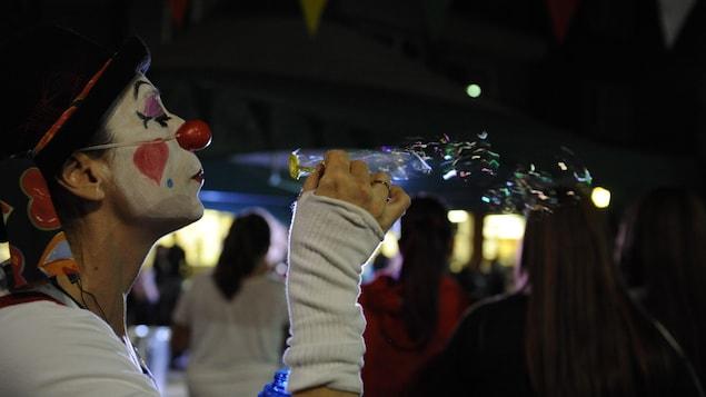 Un clown souffle pour créer des bulles dans l'air
