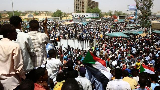 Une foule monstre est rassemblée dans un espace public au centre de Khartoum.