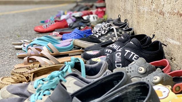 Des paires souliers par terre, sur l'asphalte.