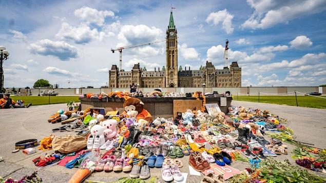 Des souliers d'enfants et des peluches près de la flamme du centenaire sur la colline du Parlement.
