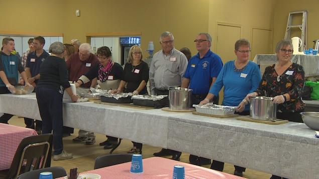 Des bénévoles se préparent à servir la nourriture pour le souper paroissial de Notre-Dame-de-Lorette.