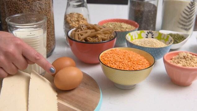 On voit du tofu, un verre de lait, deux oeurs et des bols contenant des lentilles et des céréales, disposés sur une table.