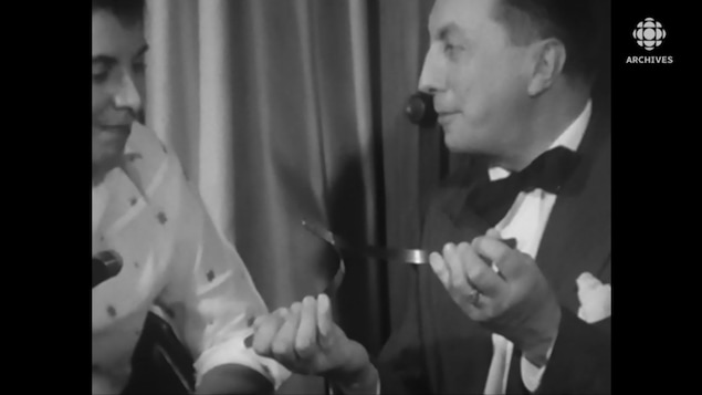 Le sourcier Henry de France montre sa baguette faite de deux baleines d'acier à la journaliste Judith Jasmin