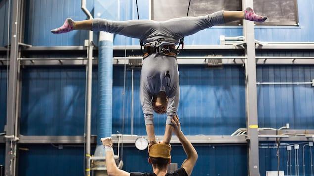 Une acrobate tente de maintenir son équilibre sur la tête de son partenaire.