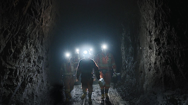 Cinq mineurs et mineures se promènent dans une mine, portant des casques équipés d'une lampe torche.