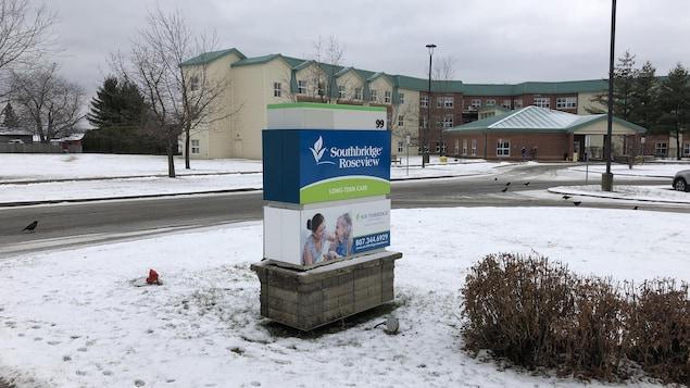L'affiche extérieure du centre de soin de longue durée est devant l'établissement sur un terrain gazonneux couvert de neige.