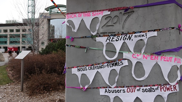 Des soutiens-gorge en papier accrochés sur un bloc de béton devant l'hôtel de ville d'Ottawa.