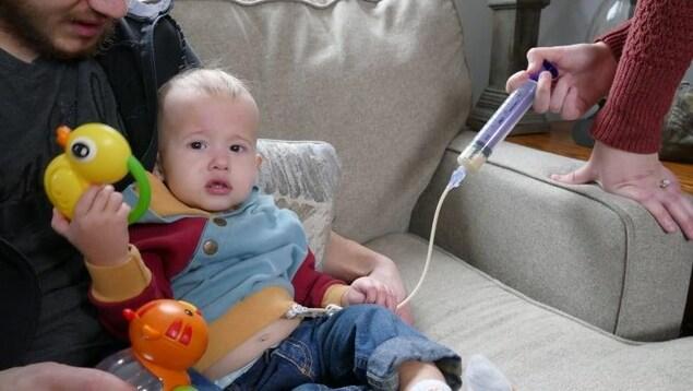 Un petit garçon dans les bras d'un homme assis. Une main de femme qui tient une seringue liée à un trou sur le ventre du petit garçon à travers un petit tuyau.
