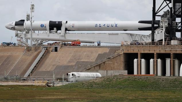 Une fusée surmontée d'une capsule est à l'horizontale, soutenue par une immense structure métallique qui, elle-même, repose sur une structure de béton.