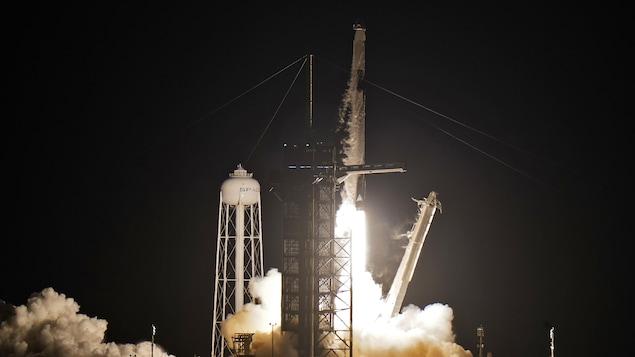 La fusée décolle dans une gerbe de feu, sur fond d'obscurité.