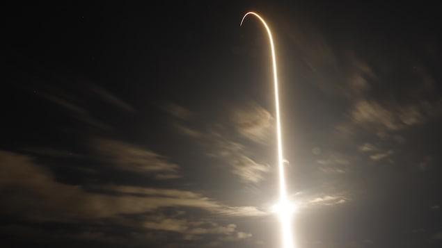 Un long rai lumineux marque la trajectoire de la fusée dans le ciel.