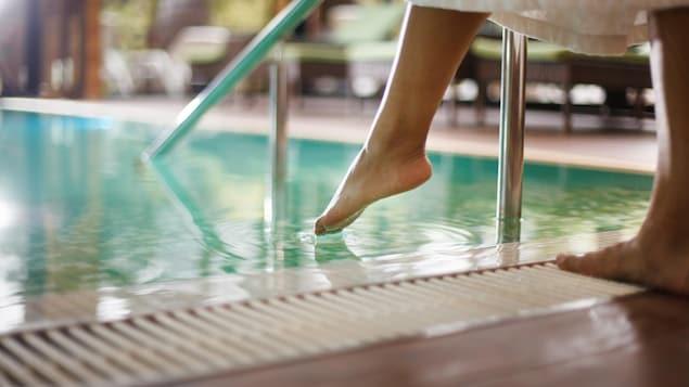 Une personne portant un peignoir trempe ses orteils dans l'eau d'une piscine.