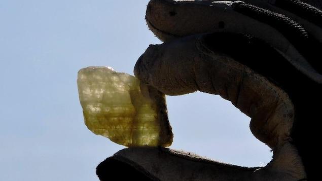 On voit une main gantée tenant un cristal de spodumène devant un ciel ensoleillé.