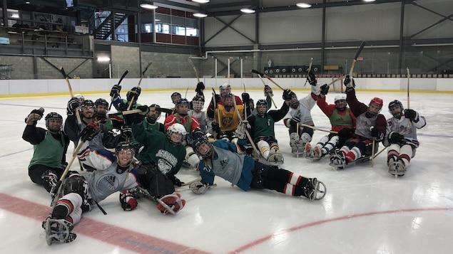 Une vingtaine de joueurs de para-hockey sourient au centre de la glace.