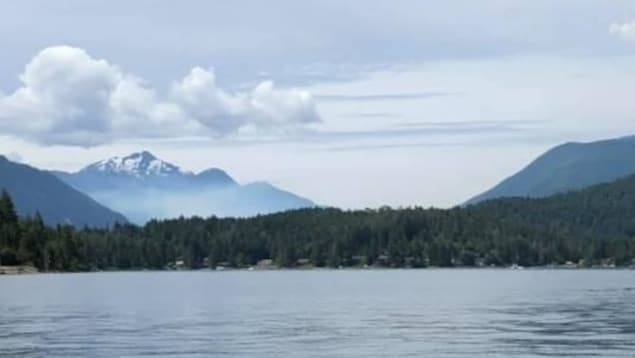 Un lac, une forêt, des montagnes et de la fumée.
