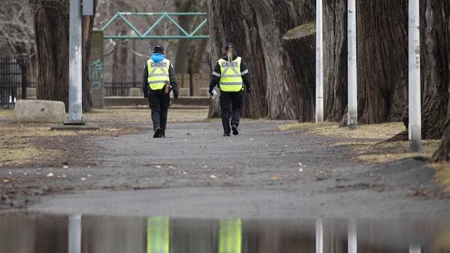 Deux cadets du SPVM marchent côte à côte dans un parc.