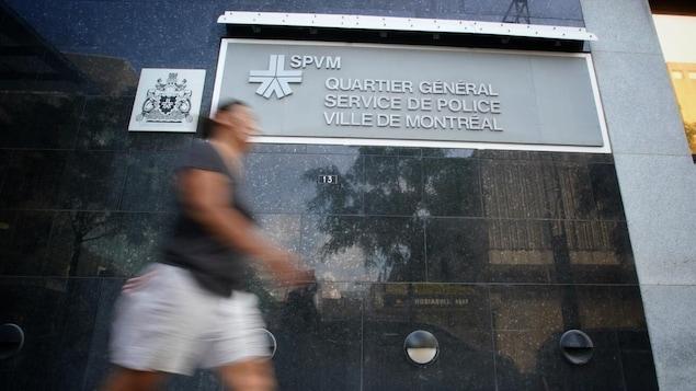 Une personne floue passe devant le quartier général du service de police de la Ville de Montréal.