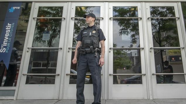Un policier devant une porte d'entrée.