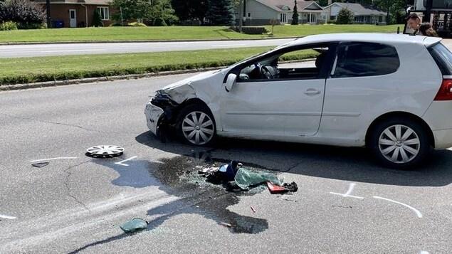Une voiture dont l'avant est amochée est au milieu de la rotue.