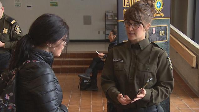 Une policière parle à une étudiante