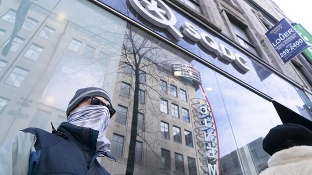 Un homme ayant remonté son chandail pour se cacher le visage attend devant une succursale de la Société québécoise du cannabis.
