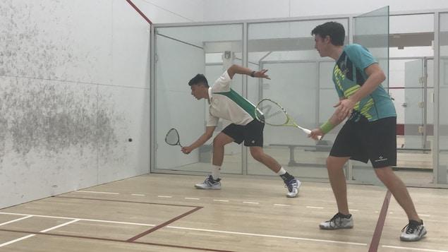 Deux joueurs de squash disputent une partie amicale.