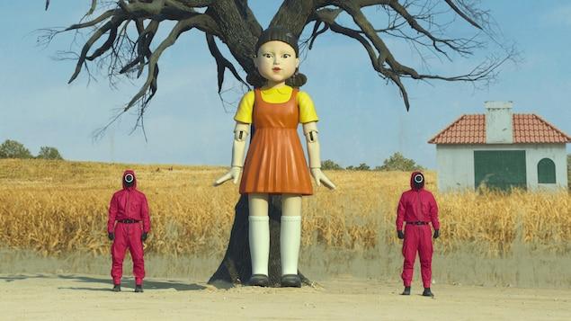 Une poupée géante est entourée de deux hommes en rouge.