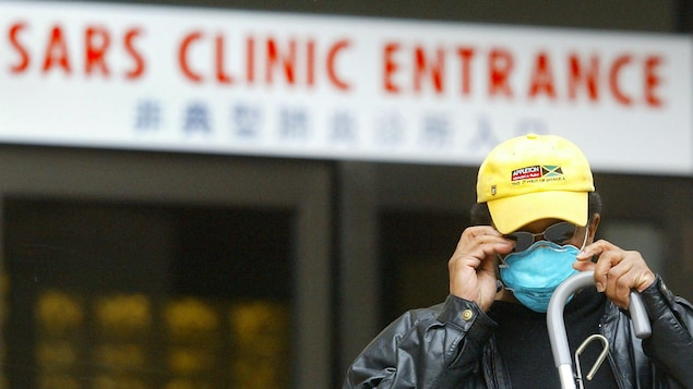 A man adjusts his protective mask as he leaves the SARS Clinic at Women's College Hospital in Toronto Friday, March 28, 2003. THE CANADIAN PRESS/ Kevin Frayer