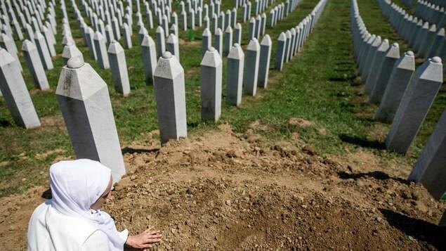 La femme touche la terre devant des milliers de stèles funéraires.